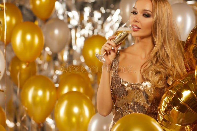 Vaya de fiesta la celebración, mujer joven magnífica en vestido de oro imagenes de archivo