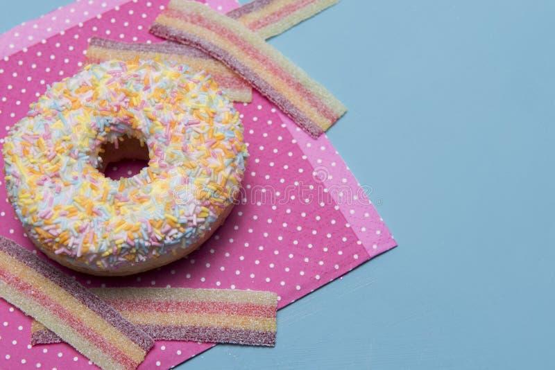Vaya de fiesta la imagen de fondo con un buñuelo y dulces coloridos del caramelo imágenes de archivo libres de regalías