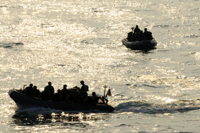 VBSS boat riders. Members of the Navy`s Visit Board Search and Seizure team prepare to board a vessel during sunset in the Persian Gulf stock photography