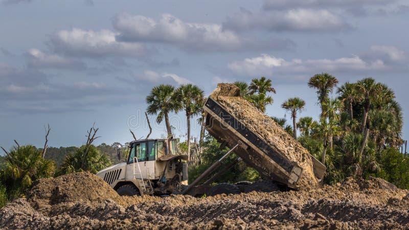 Veículo da construção - o caminhão basculante despeja a carga da sujeira em um pantanal de Florida imagens de stock royalty free