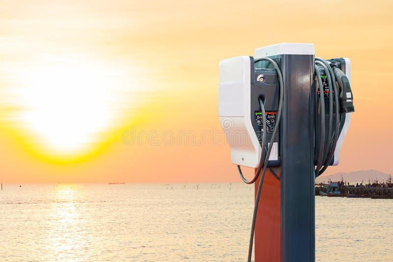 Veículo elétrico que carrega a estação de Ev com a tomada da fonte do cabo distribuidor de corrente para o carro de Ev no fundo d imagem de stock