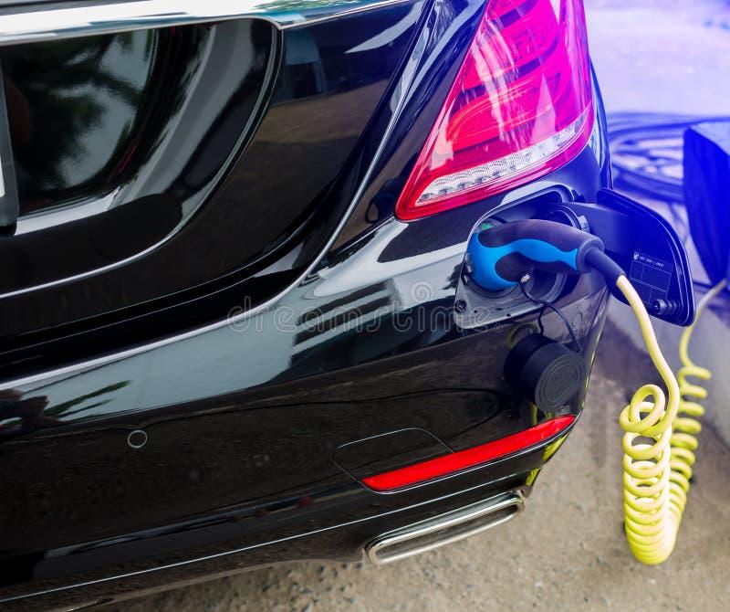 Veículo EV ou carro elétrico na estação de recarga com o cabo de alimentação conectado, carregando carro híbrido, alternati fotografia de stock