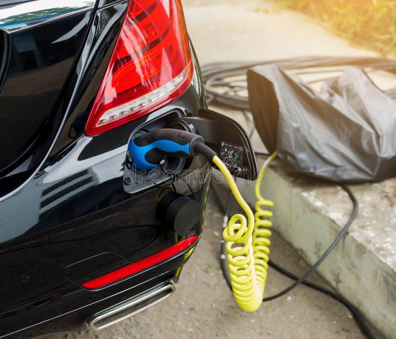 Veículo EV ou carro elétrico na estação de recarga com o cabo de alimentação conectado, carregando carro híbrido, alternati fotografia de stock royalty free