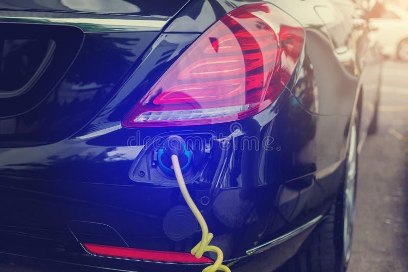 Veículo EV ou carro elétrico na estação de recarga com o cabo de alimentação conectado, carregando carro híbrido, alternati fotos de stock royalty free