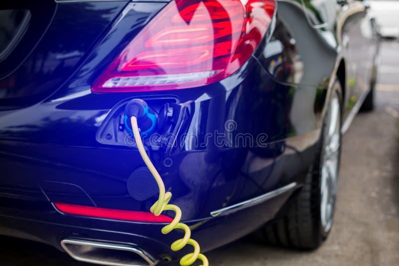 Veículo EV ou carro elétrico na estação de recarga com o cabo de alimentação conectado, carregando carro híbrido, alternati fotos de stock