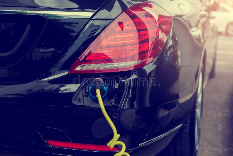 Veículo EV ou carro elétrico na estação de recarga com o cabo de alimentação conectado, carregando carro híbrido, alternati imagens de stock