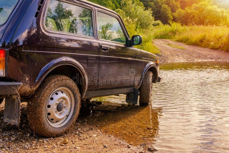 Veículo fora de estrada em um baixio através do rio na luz de incandescência do nascer do sol imagem de stock royalty free