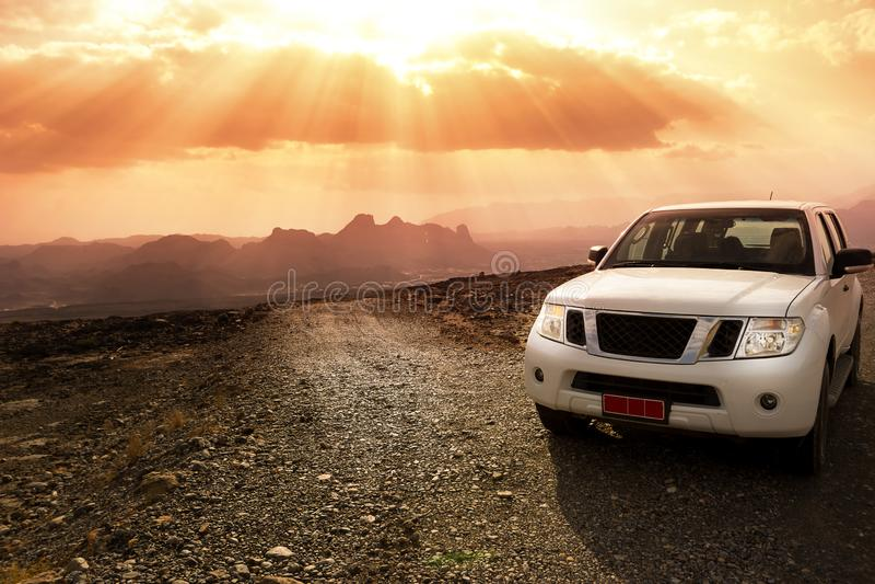 Veículo fora de estrada nas montanhas dos logros de Jebel e no céu nebuloso com raios de sol de surpresa imagem de stock royalty free