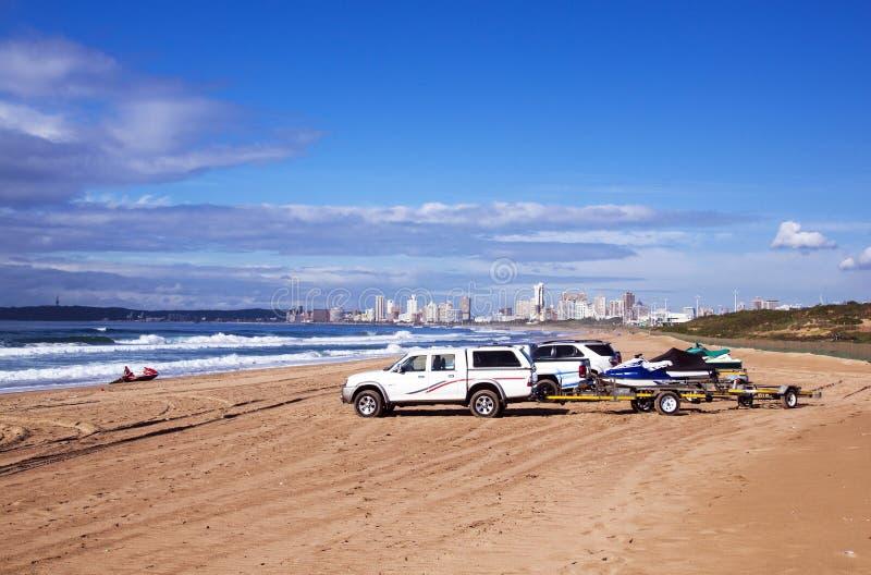 Veículos na praia contra a skyline Durban África do Sul da cidade imagem de stock