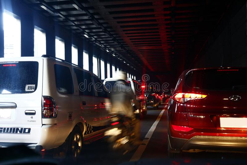 Veículos particulares e públicos e outros veículos que atravessem um cruzamento congestionado na cidade de Makati fotografia de stock