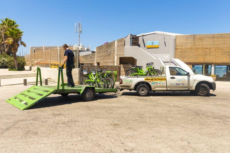 Veículos que transportam bicicletas no parkingl a praia e a frente marítima mediterrânea Vista Tel Aviv imagem de stock royalty free