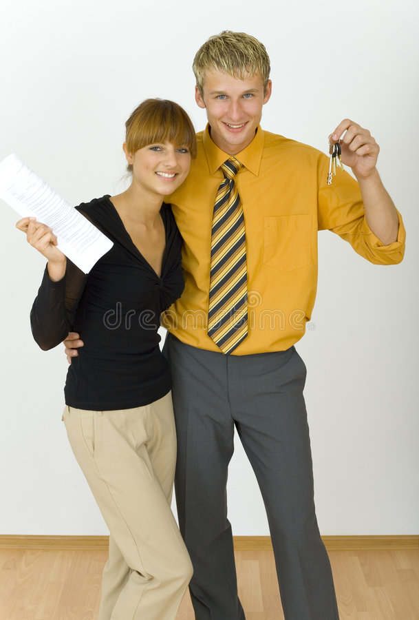 We've bought a flat!. Young, happy business couple. Man is holding keys, woman is holding some kind of contract. Looking at camera, front view stock photos