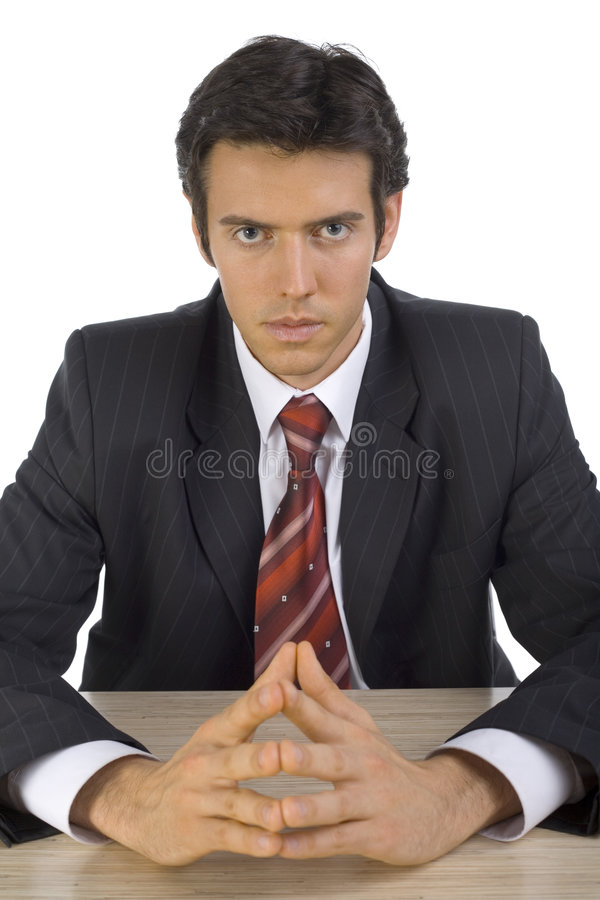 We've got to talk. Serious, handsome businessman. Seating behind desk. White background, front stock photography