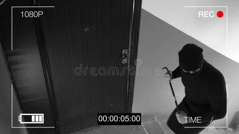 Vea el CCTV como ladrón que se rompe adentro a través de la puerta con una palanca imagen de archivo