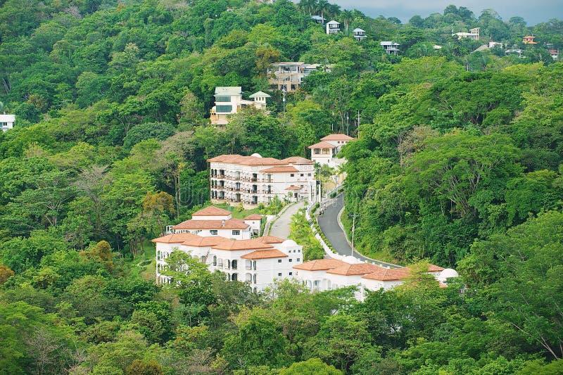 Vea a los hoteles los edificios en bosque tropical en Quepos, Costa Rica fotografía de archivo