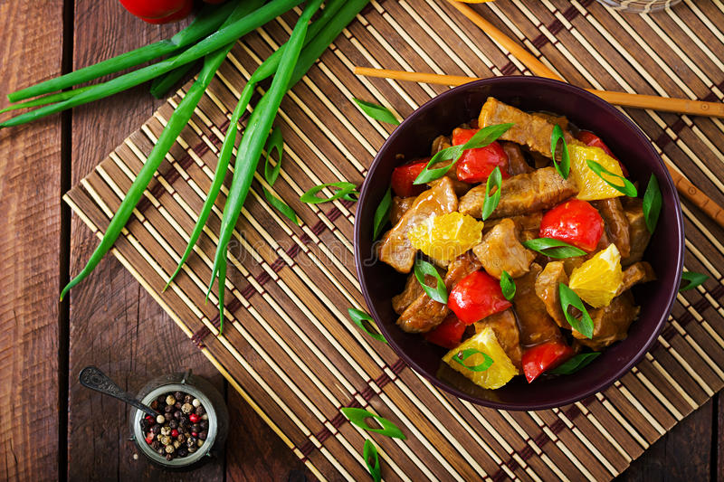 Veal fillet - stir fry with oranges and paprika in sweet and sour sauce. On a wooden background. Flat lay. Top view stock photo