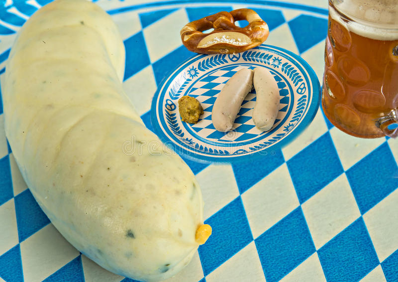 Veal sausage dish on Oktoberfest. With pretzel, beer mug and close-up of a veal sausage royalty free stock photos