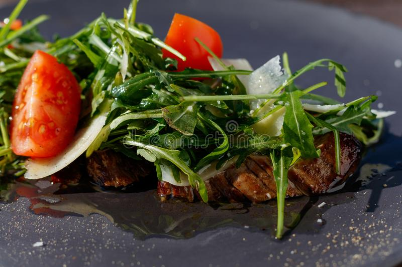 Veal steak salad with arugula, lettuce, halves of small cherry tomatoes, Parmesan cheese royalty free stock image