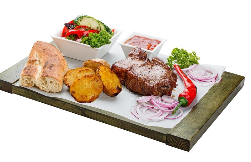 Veal steak with vegetable salad, potatoes and sauce. On a wooden board stock image