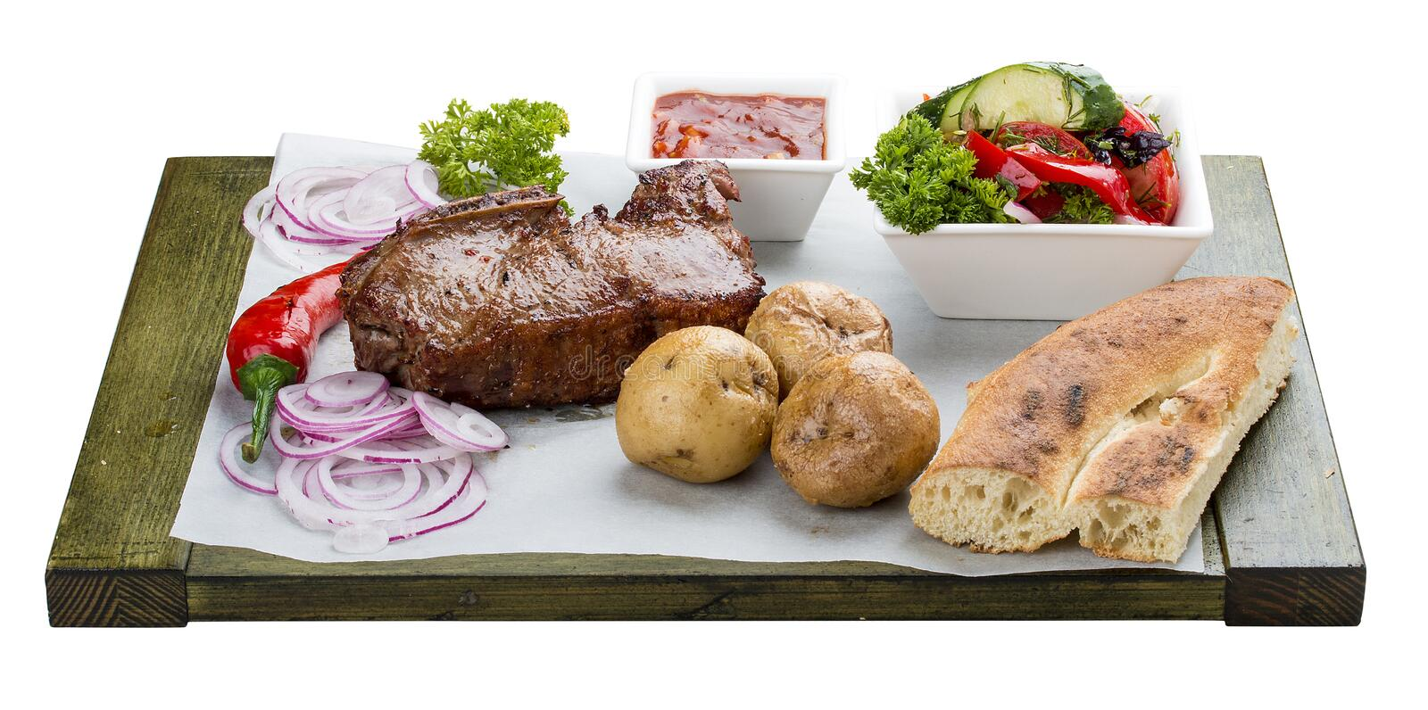 Veal steak with vegetable salad, potatoes and sauce. On a wooden board royalty free stock photo