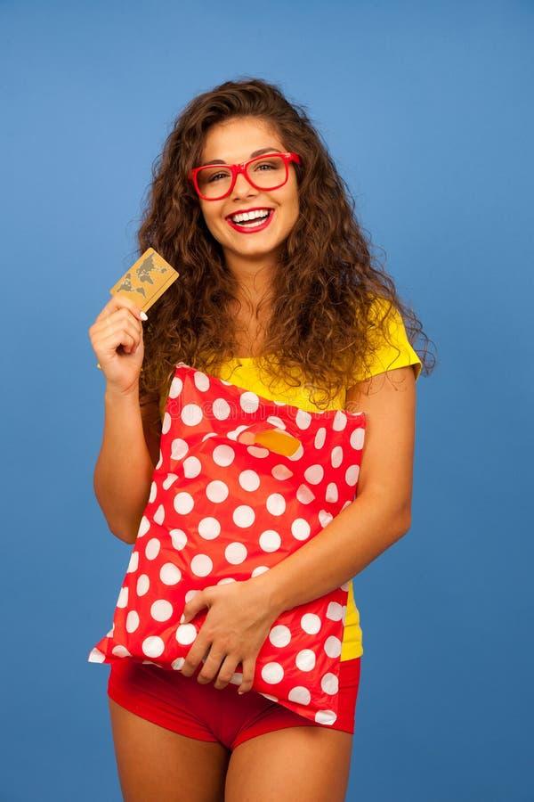 Veautiful ung kvinna med shoppingpåsar och kreditkort över blå bakgrund arkivfoto