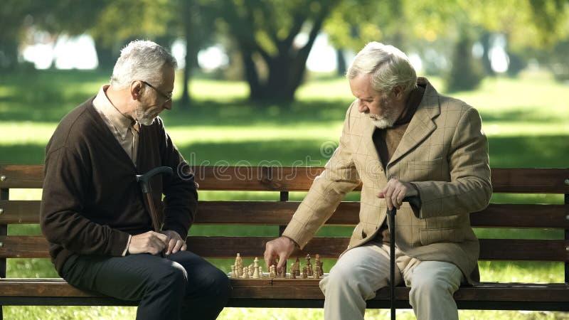 Vecchi amici che si siedono sul banco in parco e che giocano scacchi, tempo libero felice fotografia stock