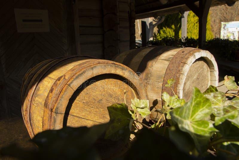 Vecchi barilotti di vino sul fondo di legno della porta con il globo arrugginito del barilotto all'aperto immagini stock libere da diritti