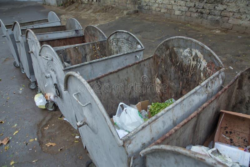 Vecchi bidoni della spazzatura verdi sulla via Rifiuti domestici nella città E Raccolta dei rifiuti dell'oggetto vicino fotografie stock