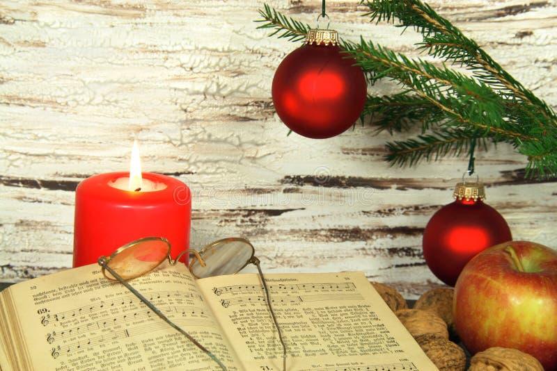 Vecchi canzoniere, decorazione di natale e candela fotografia stock