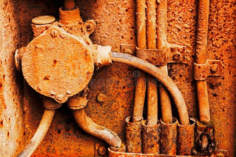 Vecchi cavi elettrici sulla parete arrugginita del ferro fotografia stock
