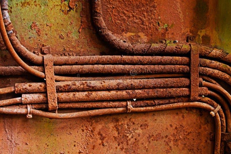 Vecchi cavi elettrici sulla parete arrugginita sporca del ferro immagini stock libere da diritti