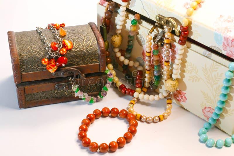 Vecchi contenitori di gioielli chiusi con le multi perle colorate ed il braccialetto di pietra naturale fotografia stock libera da diritti