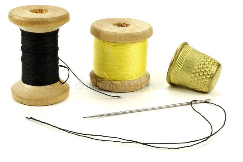 Vecchi ditali d'ottone, bobina con i fili e un ago per il cucito su un fondo bianco fotografia stock