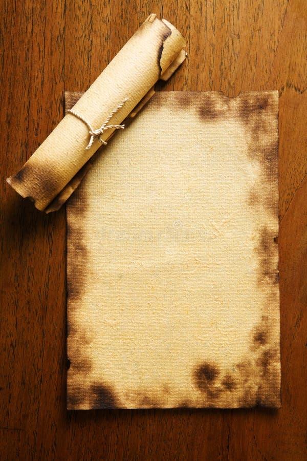 Vecchi documento in bianco e rotolo sulla tabella di legno immagini stock libere da diritti