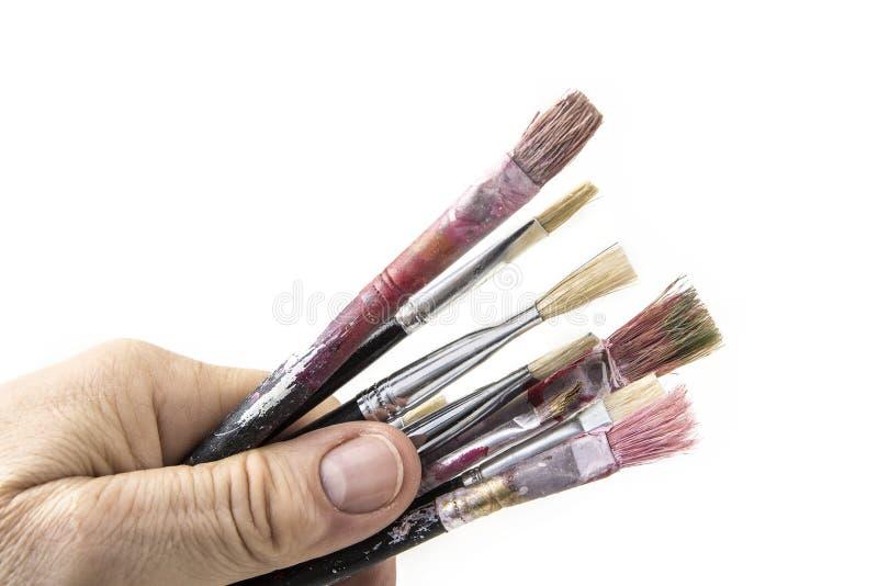 Vecchi e pennelli usati con la mano su fondo bianco fotografia stock