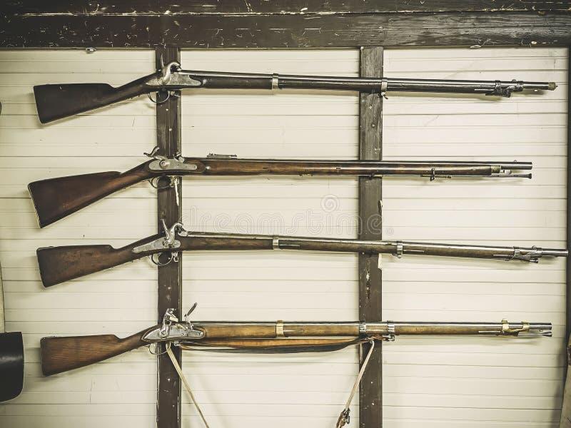 Vecchi fucili di servizio dei militari britannici con la boccetta di polvere che appende sulla parete di legno Il pezzo di uccell fotografia stock libera da diritti