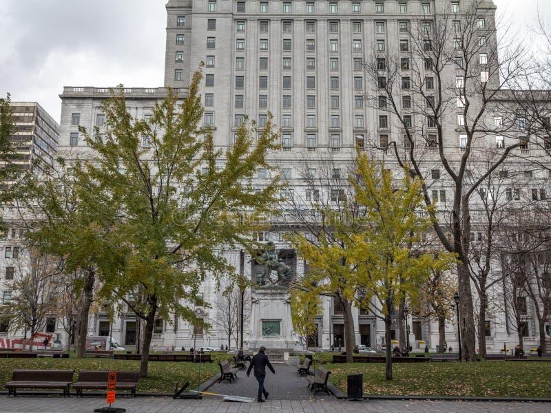 Vecchi grattacieli di pietra ed alte torri dell'ufficio di aumento a Montreal sul posto Victoria Square con un pedone che passa v immagine stock