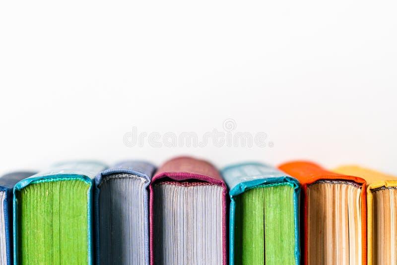 Vecchi libri che stanno in una fila su fondo bianco immagini stock