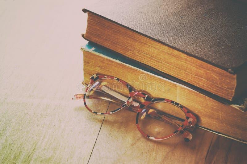 Vecchi libri con i vetri d'annata su una tavola di legno retro immagine filtrata immagini stock