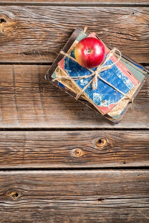 Vecchi libri e mela sullo scrittorio della scuola immagini stock libere da diritti
