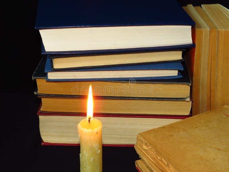 Vecchi libri impilati in un mucchio ed in una candela bruciante Istruzione, conoscenza, abitudini di lettura, carta, biblioteca,  immagini stock libere da diritti