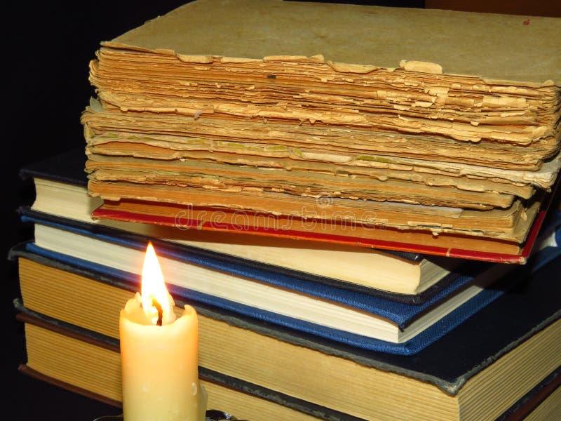 Vecchi libri impilati in una pila e una candela in fiamme Istruzione, conoscenza, abitudini di lettura, carta, biblioteca, luce,  fotografia stock libera da diritti