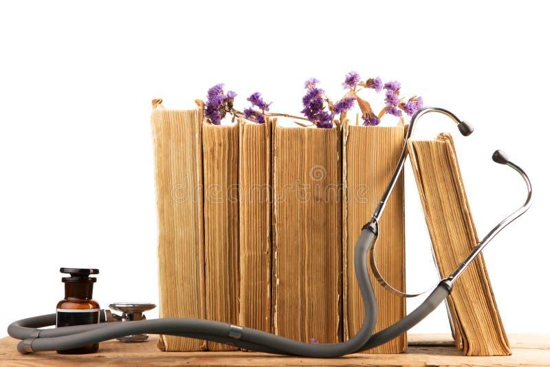 Vecchi libri medici con lo stetoscopio, bottiglia medica, medicinale lui immagini stock