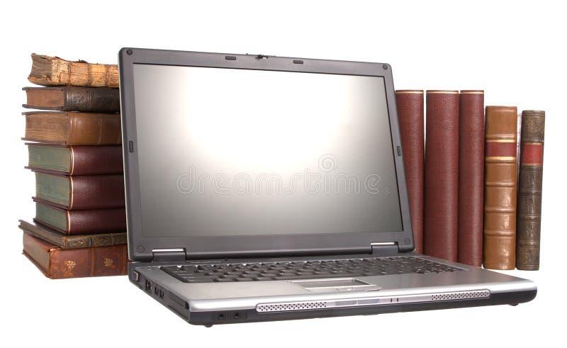 Vecchi libri rilegati di cuoio con un computer portatile immagine stock