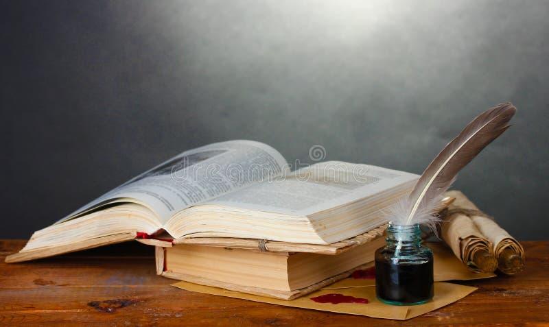 Vecchi libri, rotoli, penna della piuma ed inkwell fotografia stock libera da diritti