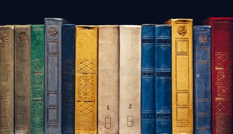 Vecchi libri in una fila in biblioteca su fondo nero con Copia-spazio immagine stock
