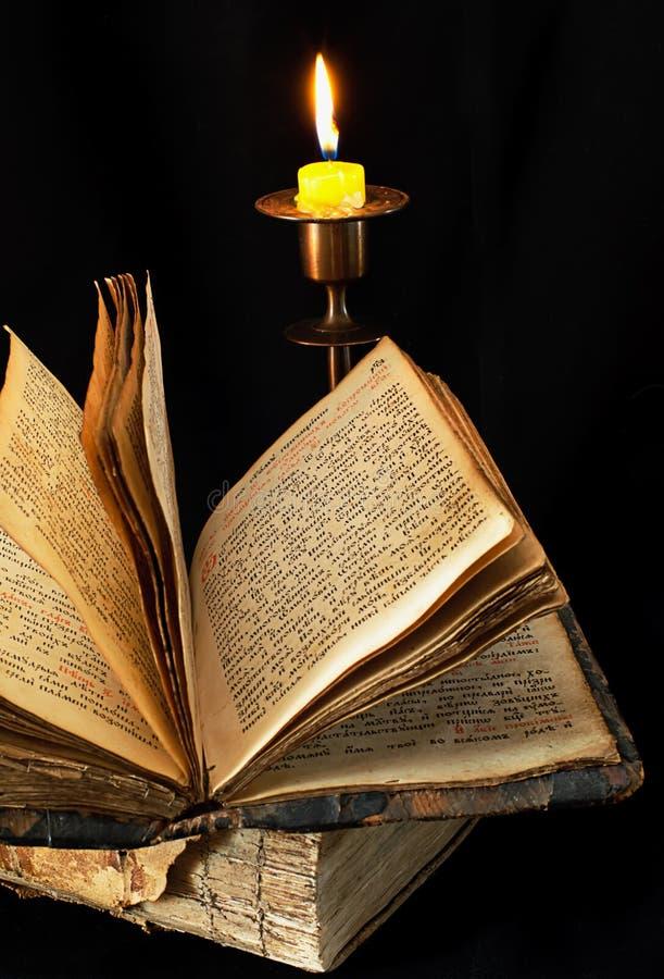 Vecchi libro e candela religiosi immagine stock