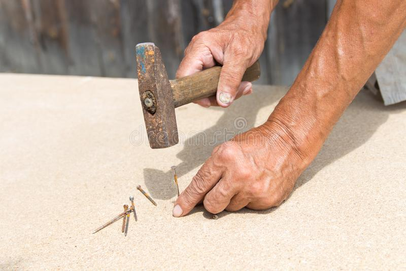 Vecchi martello e chiodo nelle mani di un uomo più anziano Il carpentiere martella un chiodo in un albero fotografie stock