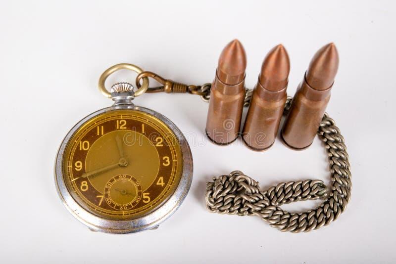 Vecchi orologio e munizioni su una tavola bianca Misura di tempo e del materiale esplosivo fotografia stock