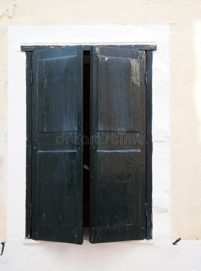 Vecchi otturatori di legno dipinti neri parzialmente aperti della finestra nel telaio bianco sulla parete di vecchia casa spagnol fotografie stock